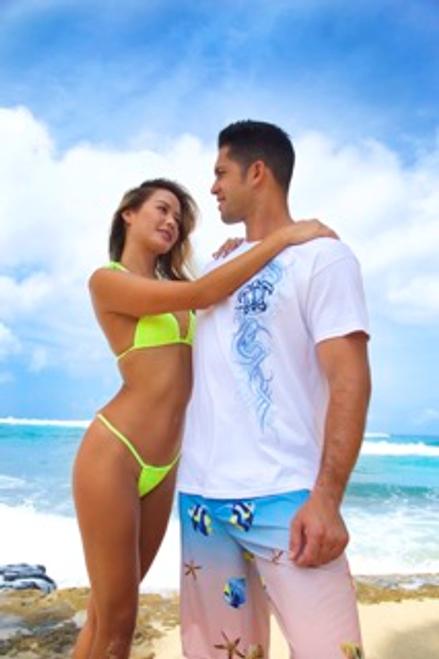Male model standing on a beach wearing Hawaiian Performance Surfwear® Crew Neck Tee - Tribal Honu in white color along a female model in bikini