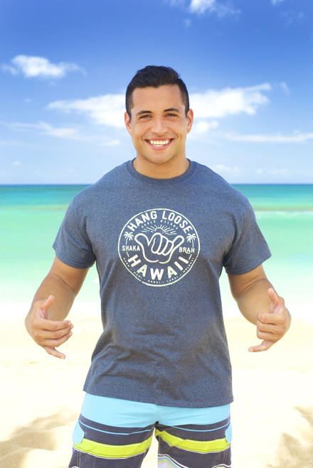 Male model wearing Hawaiian Performance Surfwear® Crew Neck Tee - Aloha Pineapple in Blue Heather color standing next to the beach **Please note: The model image may not be the design you are currently viewing. This is meant to show the style and fit of the shirt.