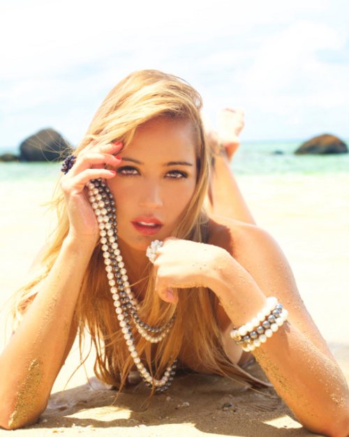 Jewel of the Sea Pearl Collection in white, black, and multi- colorations worn by a beautiful model on the white sandy beaches of Oahu