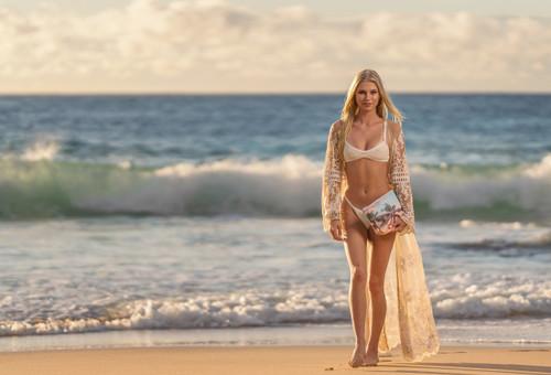 Female model in bikini carrying ENSO Large Clutch Bag in Palms design walking along a beach