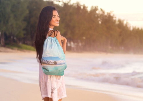 Female model standing on a beach with ENSO Beach Backpack in Wave design on her shoulder