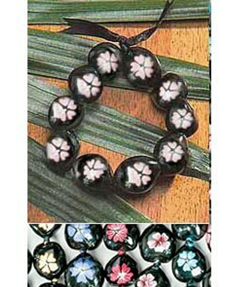Black Kukui Nut bracelet laid on a wooden table with decorative flora underneath. The bracelet has Painted Hibiscus flowers in pink. Painted Kukui Nuts are arranged below in the following colors from left to right: yellow, purple, red, white, and blue.