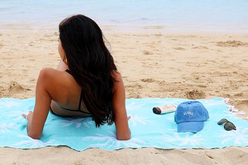Female model resting on Island Blanket in Palm Tree Teal design