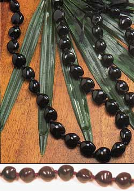 Black Kukui Nut Lei spread over wood table with decorative flora beneath.