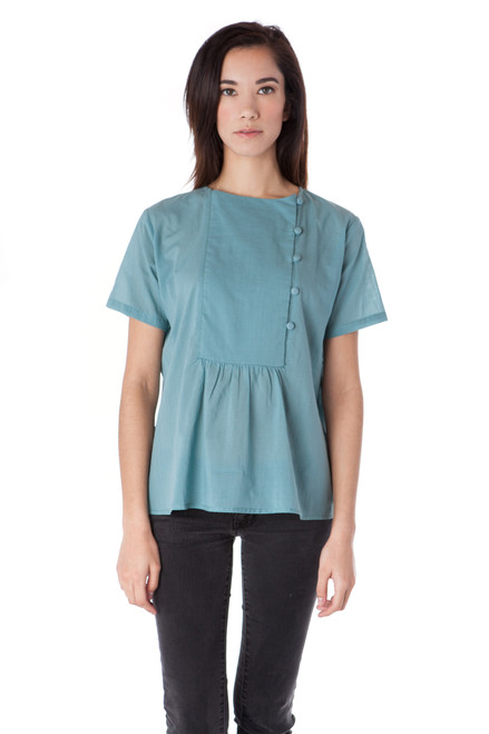 Style No. BN-116   Crafted of breezy Arctic blue cotton voile, our side button top is classic with a modern twist. This airy blouse will liven up your look without weighing you down and features a unique front panel and fabric covered buttons. Wear with your favorite dark wash skinny jeans and flats for a casual yet chic look. Machine wash with warm or cool water, and hang dry for the best wrinkle-free results.