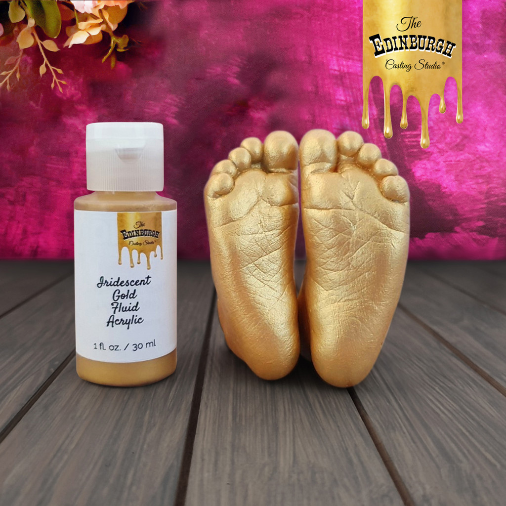 Baby feet painted with gold fluid acrylic paint