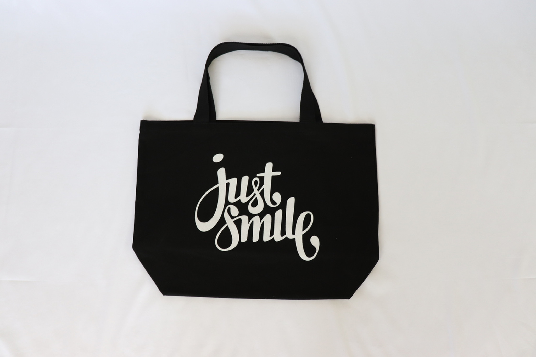 JUST SMILE BLACK CANVAS TOTE with 3 HAPPY FACES on back.