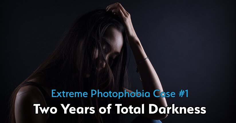 Woman with extreme photophobia in the dark holding her head