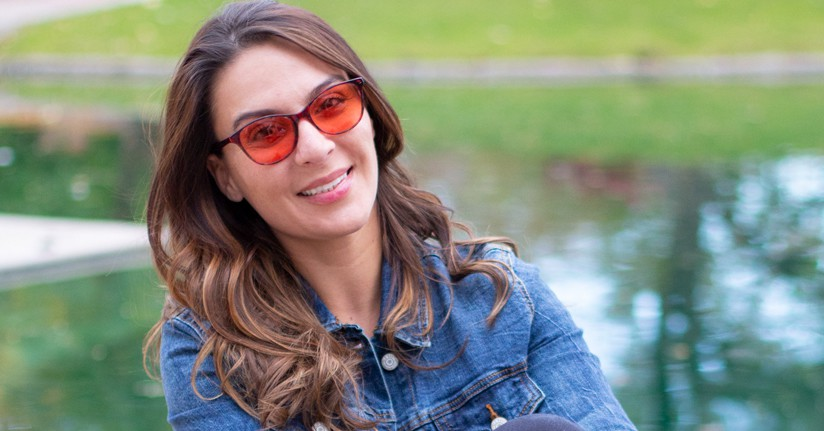 Woman wearing indoor TheraSpecs, Audrey frame, to reduce her migraine attacks and photophobia