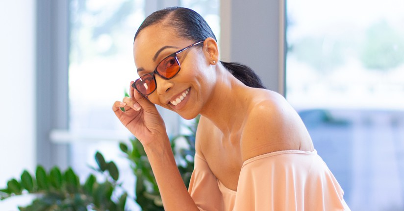 Woman wearing indoor TheraSpecs, Quinn frame, to protect from fluorescent and screen light sensitivity.