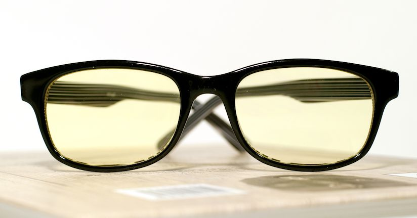 Yellow tinted blue light glasses on a box