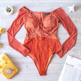 -Rust -Lace -Padded Cups -Zipper -Mesh Sleeves -Long Sleeves -Snap Closure -Partially Lined -Fabric Stretches -Comes in 4 Colors -Cheeky -Bodysuit  Model is Wearing Size Small  Material: Shell 1: 90% Polyester   10% Spandex Shell 2: 94% Polyester   6% Spandex  HMT53748 BSUIT RSTL
