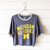 """-Heather Navy -Crew Neck -Michigan Wolverines Graphic -Short Sleeve -Cropped -T-Shirt  Size Medium  Material: Unknown  Clothing Measurements: Bust: 20"""" Length: 20.5"""" Sleeve Length: 9"""""""