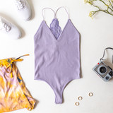 -Lavender -V-neck -Bungee Straps -Racer Back -Lace Back -Ribbed -Thong -Fabric Stretches -Comes in 4 Colors -One Size Fits Most -Bodysuit  Material: 92% Nylon | 8% Spandex  328 BSUIT PRP