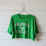 """-Green with White and Grey Writing  -Reads """"Philadelphia Eagles"""" -Crew Neck -Cropped Length -Short Sleeve -T-Shirt  Size Extra Large  Material: 100% Cotton  Clothing Measurements: Bust: 48"""" Length: 14"""" Sleeve Length: 9"""""""