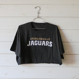 """-Black with White & Gold Print -Reads """"JACKSONVILLE JAGUARS"""" -Official NFL Pro Line -Crew Neck -Cropped Length -Short Sleeve -T-Shirt  Size 3X Large  Material: 100% Cotton  Clothing Measurements: Bust: 46"""" Length: 13"""" Sleeve Length: 9"""""""