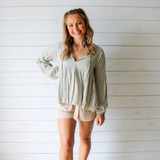 -Sage Green Color -V-Neck -Ties in Front -Puff Sleeves -Long, Relaxed Fit -Flares at Waist -Long Sleeves -Top  Materials: 95% Polyester   5% Spandex  31195TI TOP GRN