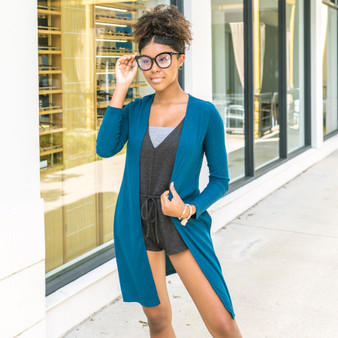 -Dark Teal -Ribbed -Side Slits -Long Sleeve -Long -Cardigan -Comes in 3 Colors  Model is Wearing Size Small  Material: 96% Polyester 4% Spandex  T2712R CARDI TEAL