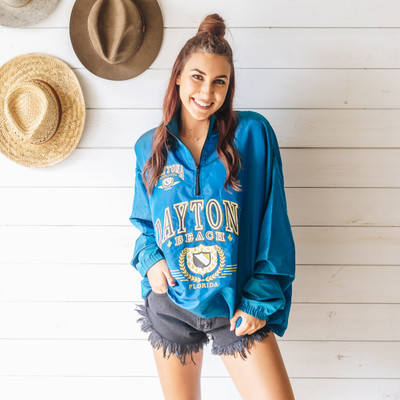 "- Quarter Zip  - Long Sleeves  - Teal Blue Jacket  - Daytona Beach Design  - Windbreaker Material  Top is a size X Large   Clothing Measurements: Bust: 27.5"" Length: 28"" Sleeve Length: 23"""