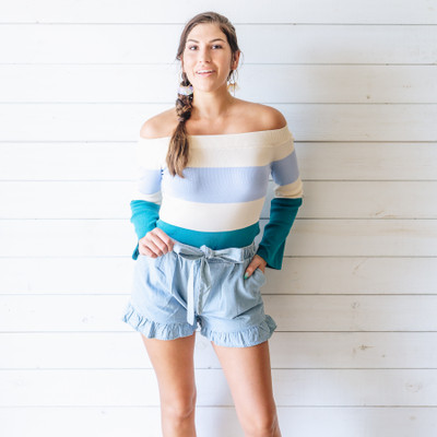 - Off the Shoulder  - Cream with Teal and Light Blue Stripes  - Long Sleeves  - Fabric Does Stretch  Model is Wearing a Size Medium   Material Content: 65% Rayon  35% Nylon   CT0437 SWTR