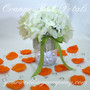 Orange Rose Petals Surround a Wedding Centerpiece