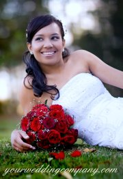 Bride laying on the grass with wedding bouquet.