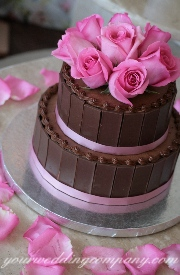 Chocolate wedding cake with pink accents.