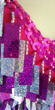 A short handmade sequin dress, with rectangular hologram silver and fuchsia mixed paillette sequins close up view