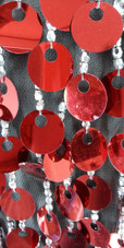 A short handmade sequin dress, in 20mm metallic red paillette sequins with silver faceted beads, a luxe grey fabric background and jagged, beaded hemline close up view