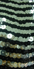 Short Swirl Patterned Handmade 10mm Flat Sequin Chinese Collar Dress in Metallic Silver and Black with Jagged and Beaded Hemline Close up view