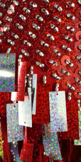 A short handmade sequin dress, with 10mm hologram red fishscale sequins overlaid with silver faceted beads close up view