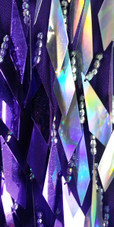 A short handmade sequin dress, with diamond-shaped metallic silver and purple sequins close up view