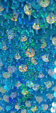 A long handmade sequin dress, in 8mm cupped hologam turquoise and silver sequins close up view