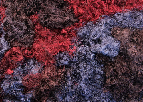 Throwsters waste silk fiber texture for feltmakers.  This dyed color is Banded Iron.