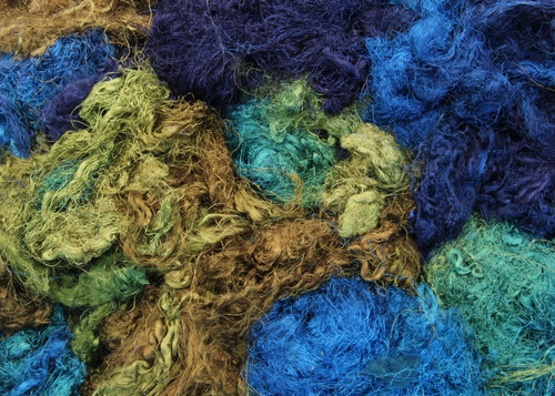 Throwsters waste silk fiber texture for feltmakers.  This dyed color is Seagrass.