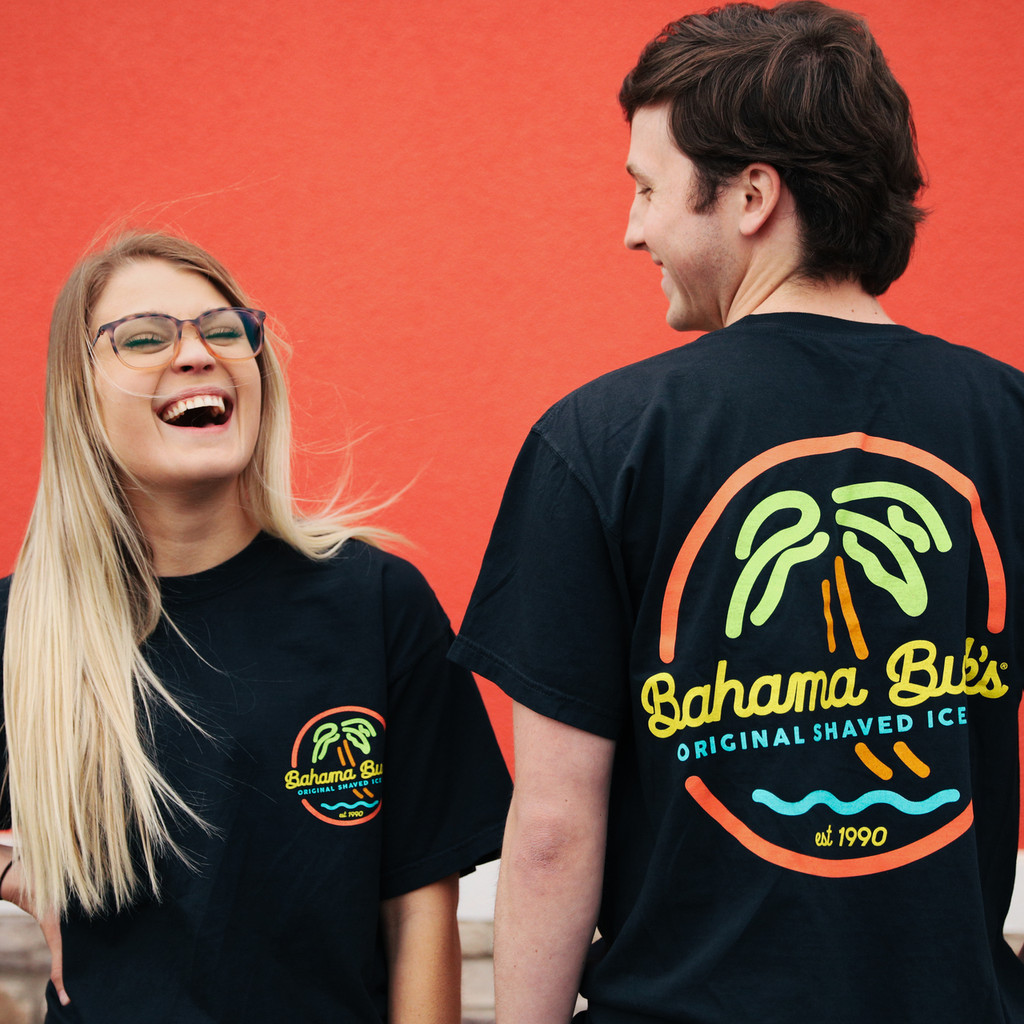 girl and boy laughing as they wear neon sign tee