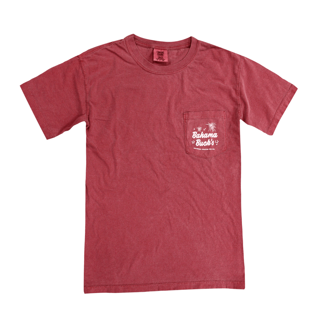 The front of the brick red, pocket Comfort Colors short-sleeve Independence Day Wagon tee. The pocket has white stars and fireworks on it with the text Bahama Buck's Original Shaved Ice Co.