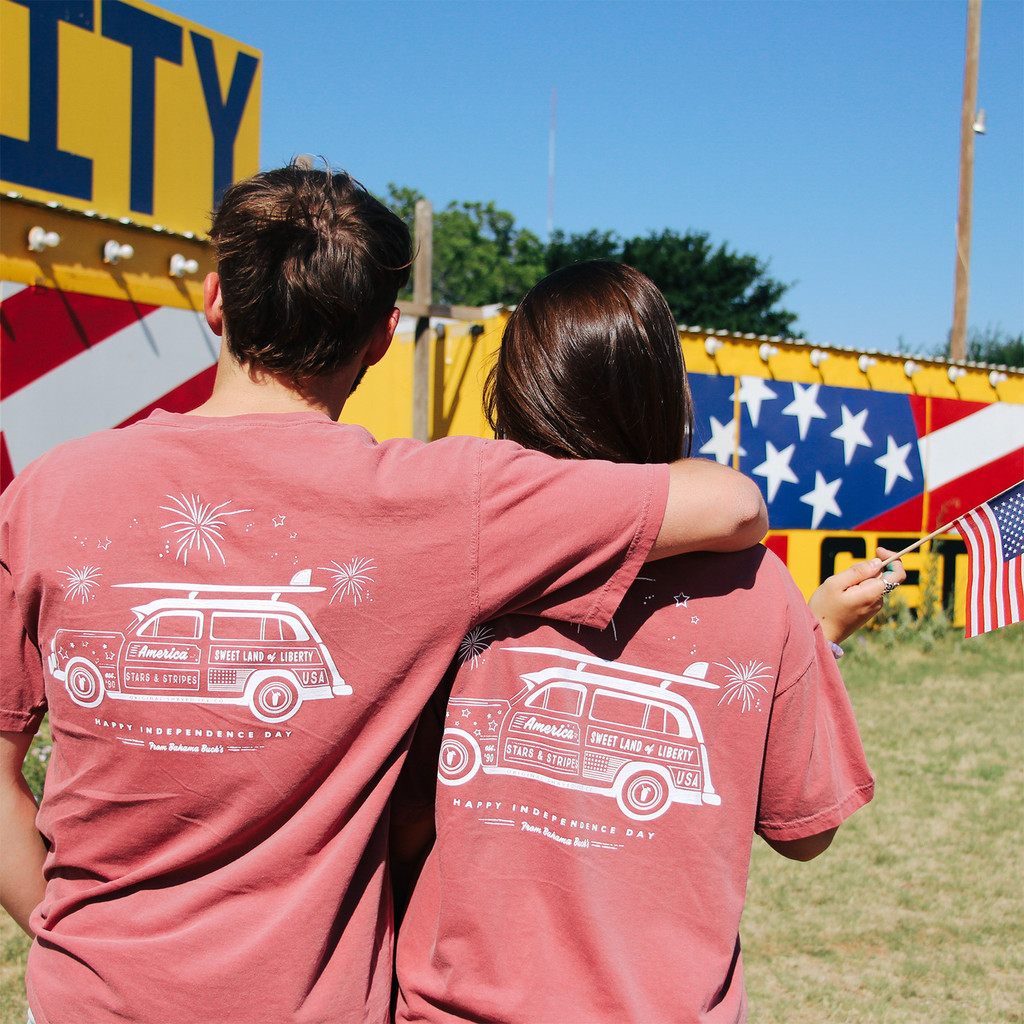A photo of a guy and girl wearing the Independence Day Wagon tee in front of a fireworks stand