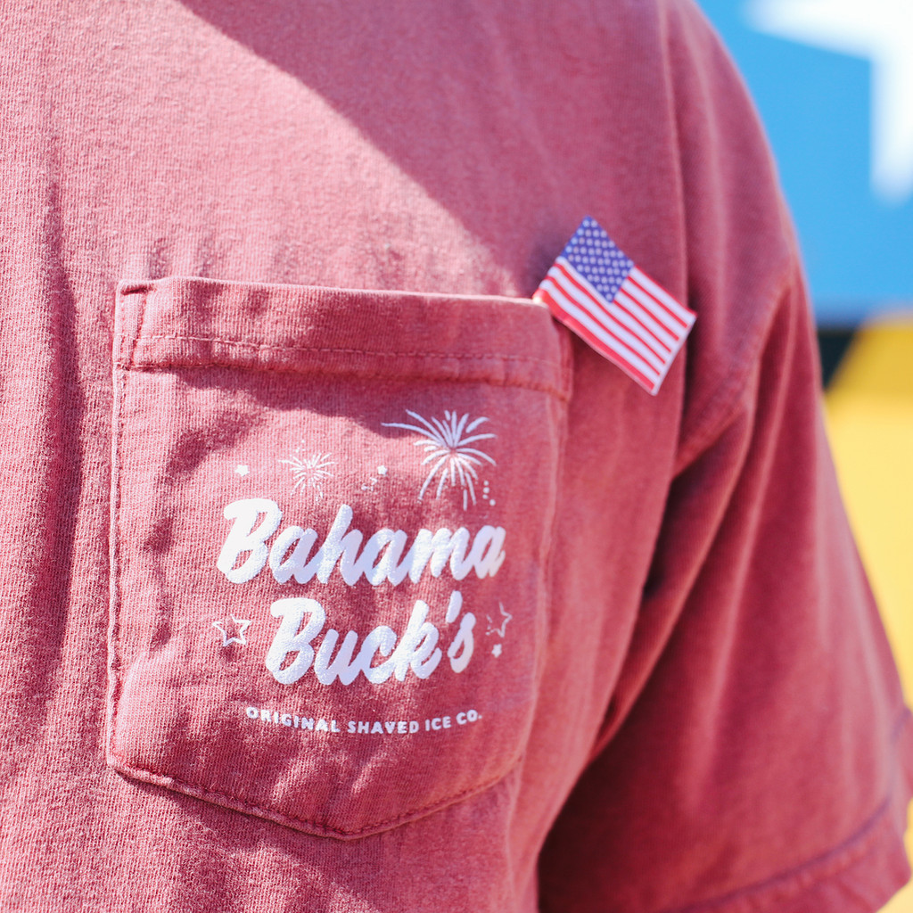 An up close photo of the front pocket of the t-shirt with a small American flag sticking out of the pocket