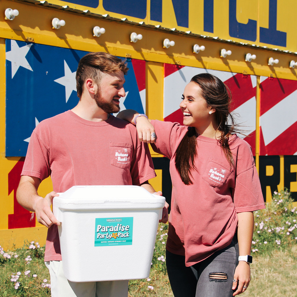 A photo of a young man holding a Sno2Throw cooler while smiling at a young woman wearing the Independence Day Wagon tee.