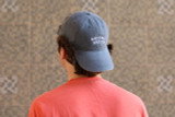 The back of a young man wearing the denim blue Bahama Buck's cap backwards