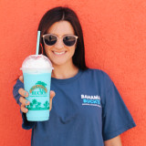 A young woman wearing a Wavebender tee and smiling while she holds out her Wavebender smoothie