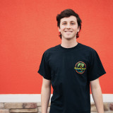 boy smiling wearing the neon sign tee