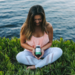 woman yoga by ocean holding spirulina tablets