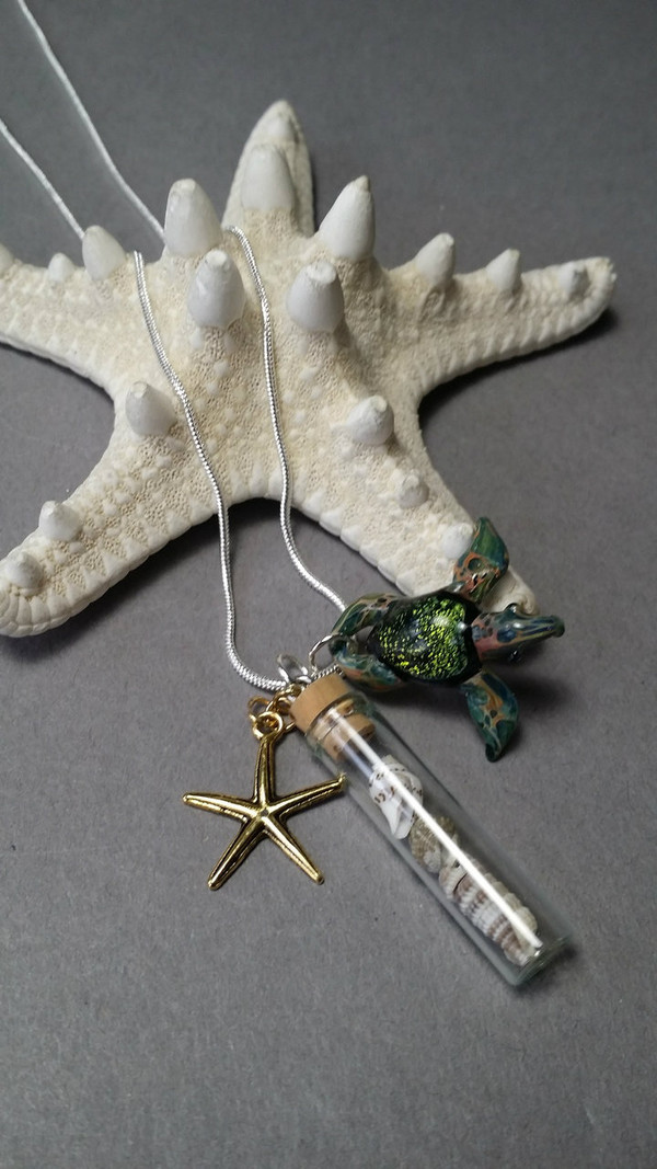 Gold star fish  with a Turtle and Glass bottle with sea shells and mounted on a silver serpentine chain