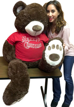 Giant Christmas Teddy Bear wears red t-shirt that says Merry Christmas