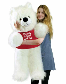"""Send this Big Plush® giant stuffed white teddy bear as your ambassador of love during quarantine. It gets delivered already wearing a removable t-shirt that reads: """"I Socially Distantly LOVE You""""."""