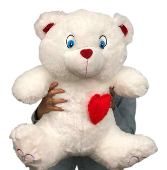 Large white teddy bear with red heart pillow on it's chest