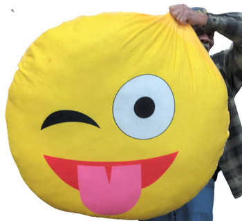 Giant stuffed emoji pillow face with tongue stuck out licking it's lips