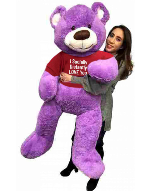 """Send this Big Plush® giant stuffed purple teddy bear as your ambassador of love during quarantine. It gets delivered already wearing a removable t-shirt that reads: """"I Socially Distantly LOVE You""""."""